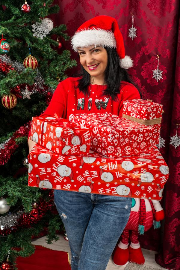 Mujer feliz que sostiene muchos regalos de la Navidad foto de archivo libre de regalías