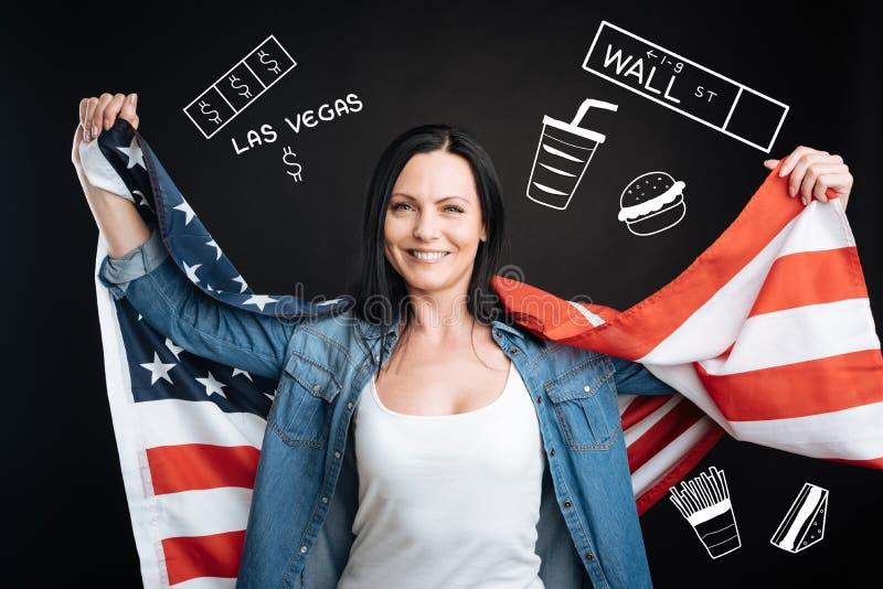 Mujer feliz que sostiene una bandera de los E.E.U.U. mientras que viaja a Los Ángeles imagen de archivo