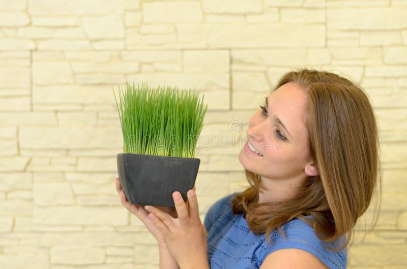Mujer feliz que sostiene una pequeña planta verde fotografía de archivo libre de regalías