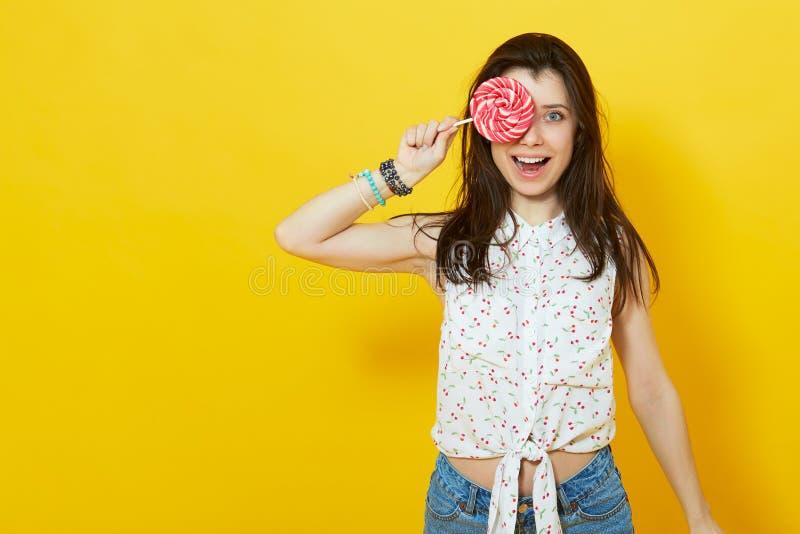 Mujer feliz que sostiene una piruleta foto de archivo libre de regalías