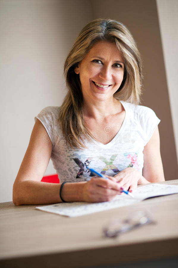Mujer feliz que termina crucigramas foto de archivo libre de regalías