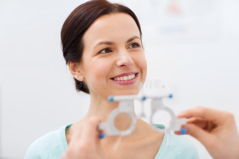 Mujer feliz que tiene prueba de la visión en la clínica de ojo foto de archivo