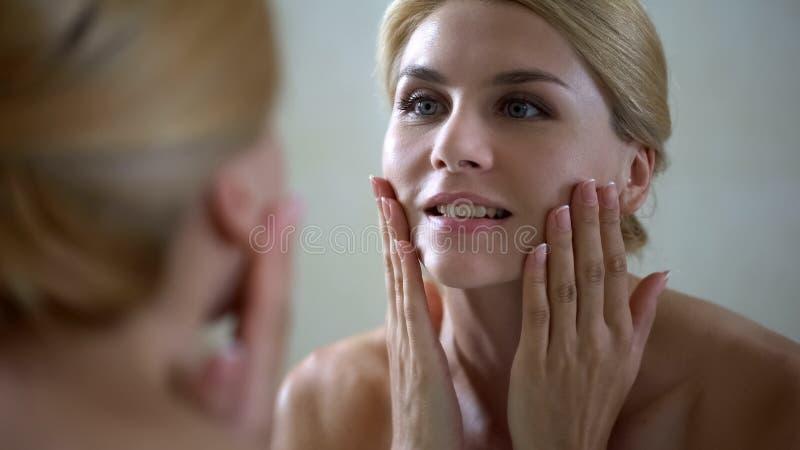 Mujer feliz que toca la cara, buen efecto de la loción antienvejecedora, skincare diario imagen de archivo libre de regalías