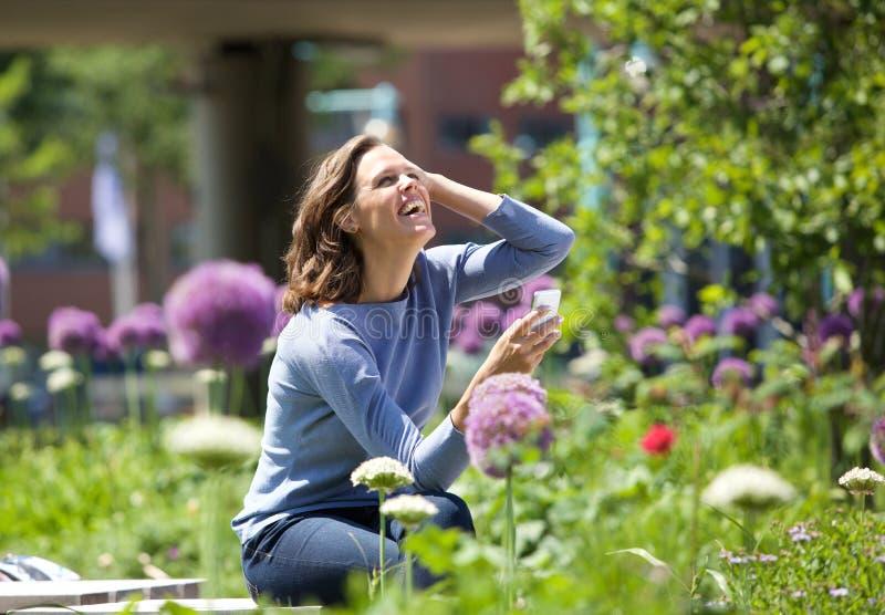 Mujer feliz que toma la fotografía de flores en parque imágenes de archivo libres de regalías