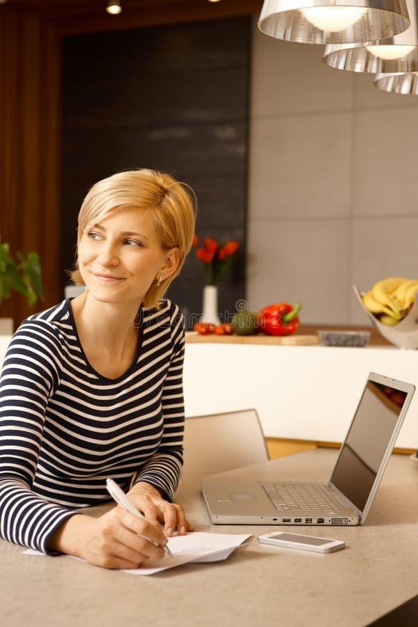 Mujer feliz que trabaja en casa imagen de archivo