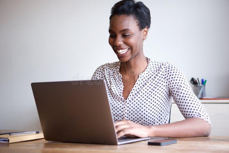Mujer feliz que trabaja en el ordenador portátil de Ministerio del Interior imagen de archivo