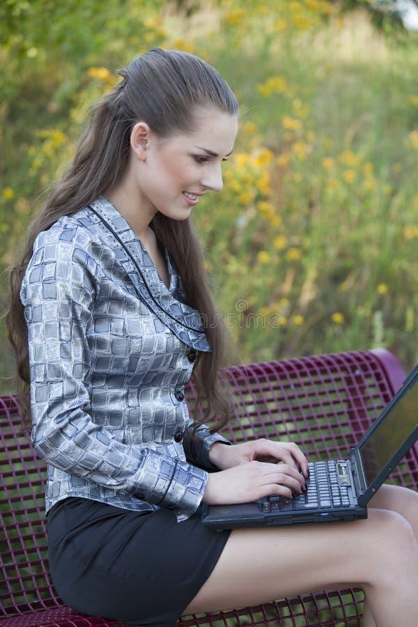 Mujer feliz que trabaja en la computadora portátil imagenes de archivo