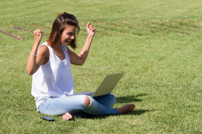 Mujer feliz que usa el ordenador portátil foto de archivo libre de regalías