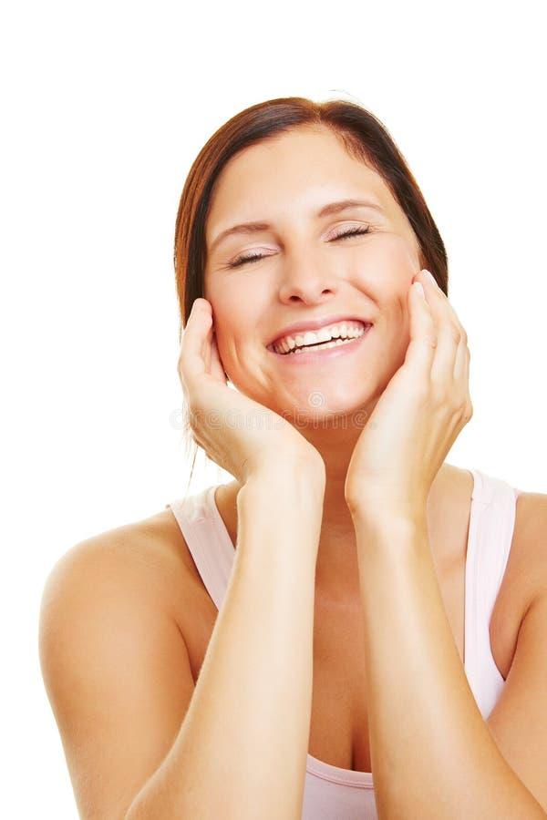 Mujer feliz que usa la crema hidratante para el cuidado de piel imagen de archivo