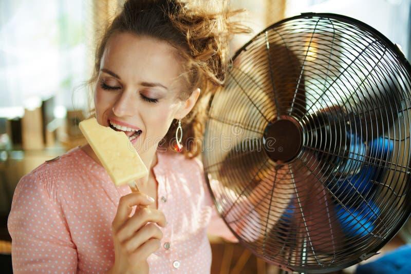Mujer feliz que usa la fan metálica eléctrica mientras que come el helado imagenes de archivo