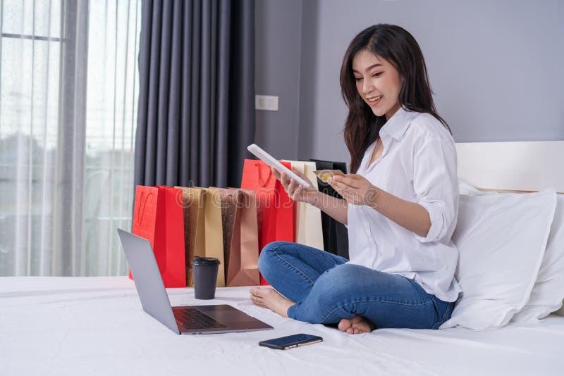 Mujer feliz que usa la tableta para las compras en línea con la tarjeta de crédito encendido fotografía de archivo libre de regalías