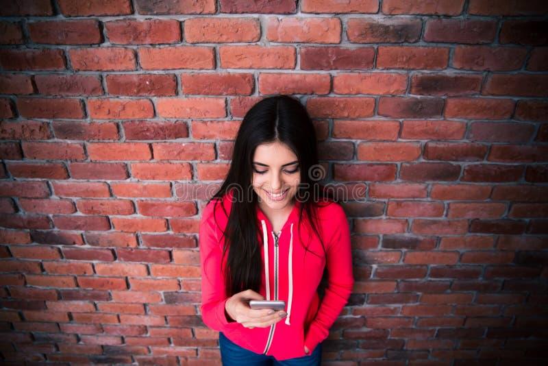 Mujer feliz que usa smartphone sobre la pared de ladrillo foto de archivo