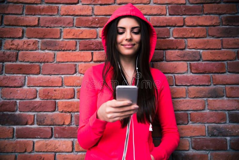 Mujer feliz que usa smartphone sobre la pared de ladrillo fotografía de archivo