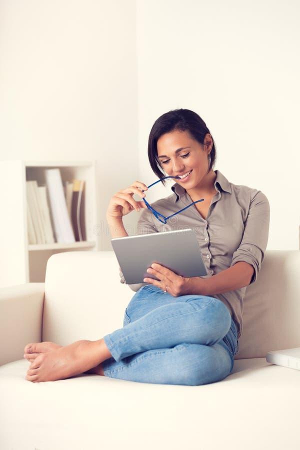 Mujer feliz que usa una tableta del digialt que se sienta en un sofá imagen de archivo libre de regalías