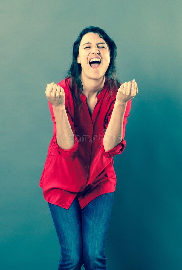 Mujer feliz 30s que grita con lenguaje corporal eufórico fotos de archivo