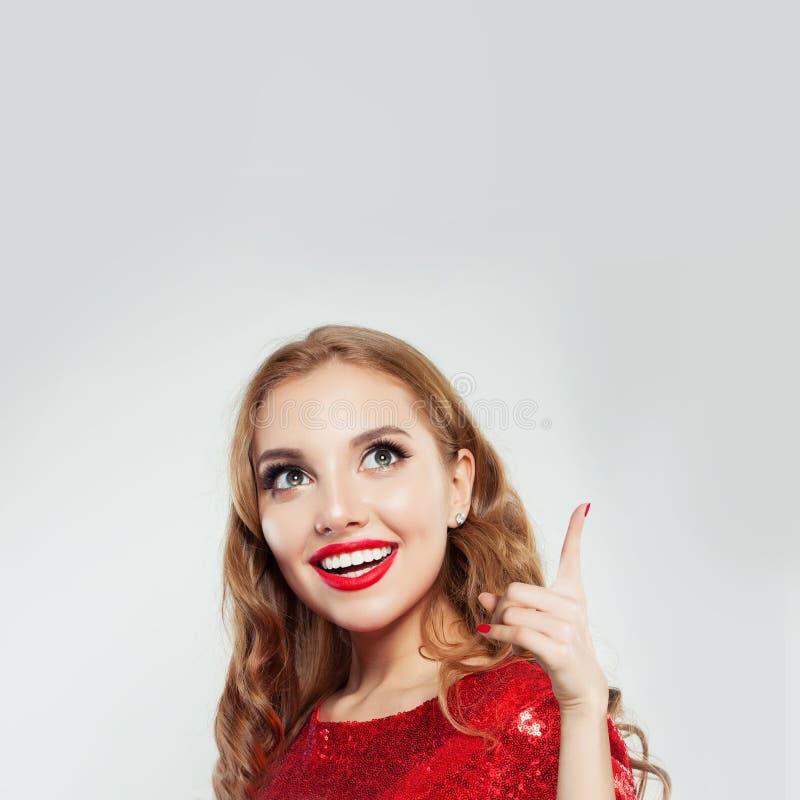 Mujer feliz salida que señala para arriba en el fondo blanco con el espacio de la copia imagen de archivo libre de regalías