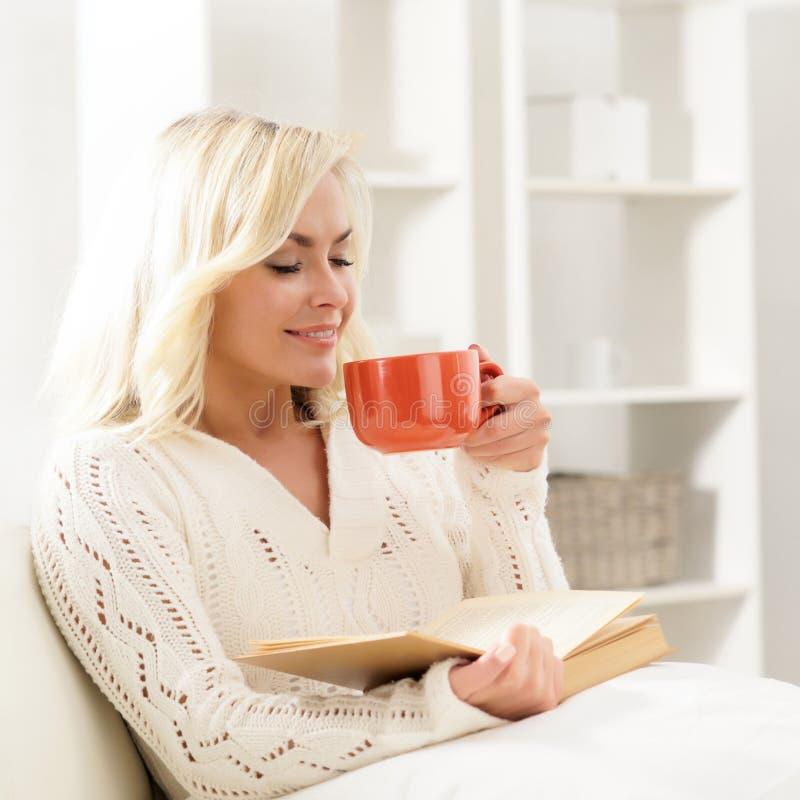 Mujer feliz sonriente atractiva que lee un libro imagen de archivo