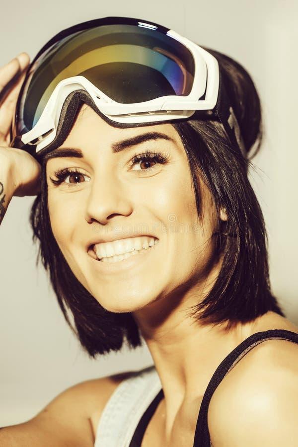 Mujer feliz sonriente bonita en gafas del esquí o gafas de seguridad fotografía de archivo