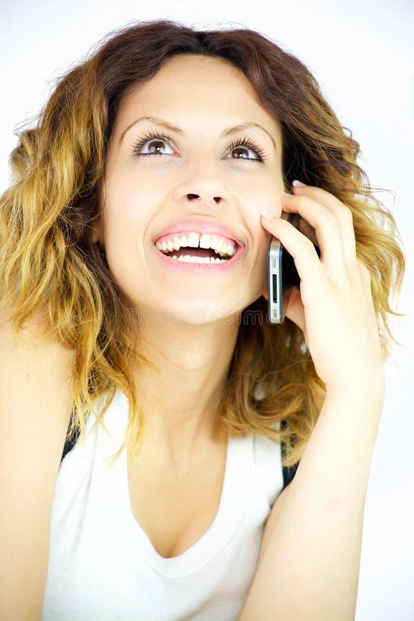 Mujer feliz sonriente en el teléfono por completo de la alegría foto de archivo libre de regalías