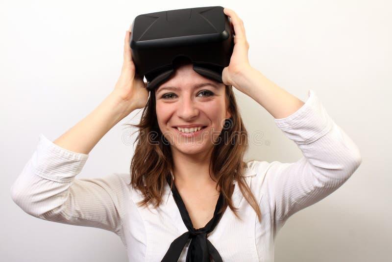 Mujer feliz, sonriente en una camisa blanca, auriculares de la realidad virtual 3D de la grieta VR de Oculus que llevan, quitándo imagen de archivo