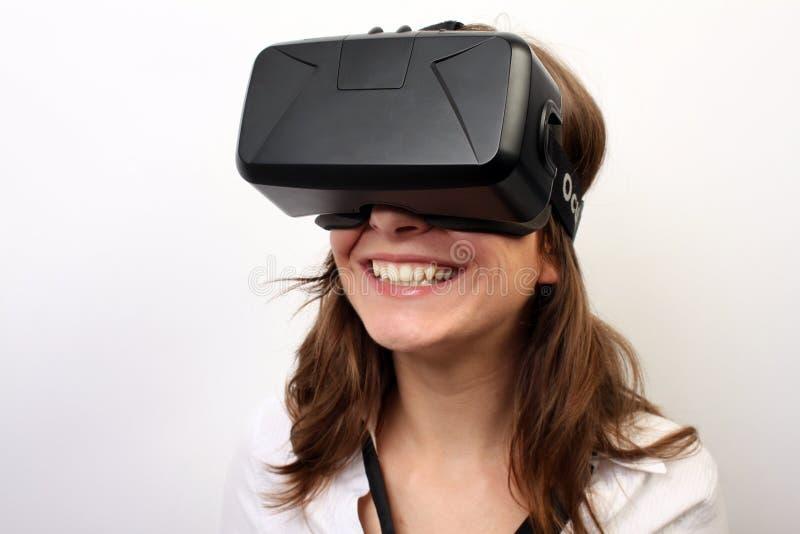Mujer feliz, sonriente en una camisa blanca, auriculares de la realidad virtual 3D de la grieta VR de Oculus que llevan, riendo imagen de archivo