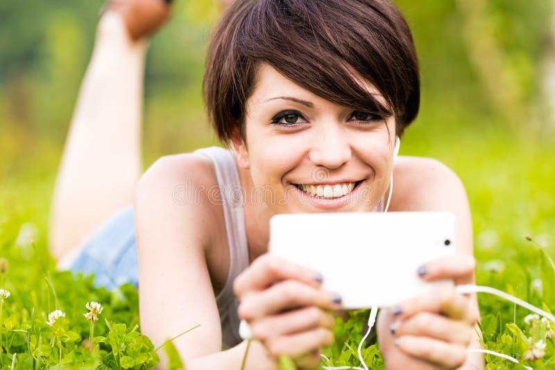 Mujer feliz sonriente que escucha la música al aire libre fotos de archivo libres de regalías
