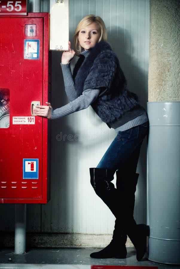 Mujer feliz sonriente que presenta en el estacionamiento del garage imagenes de archivo