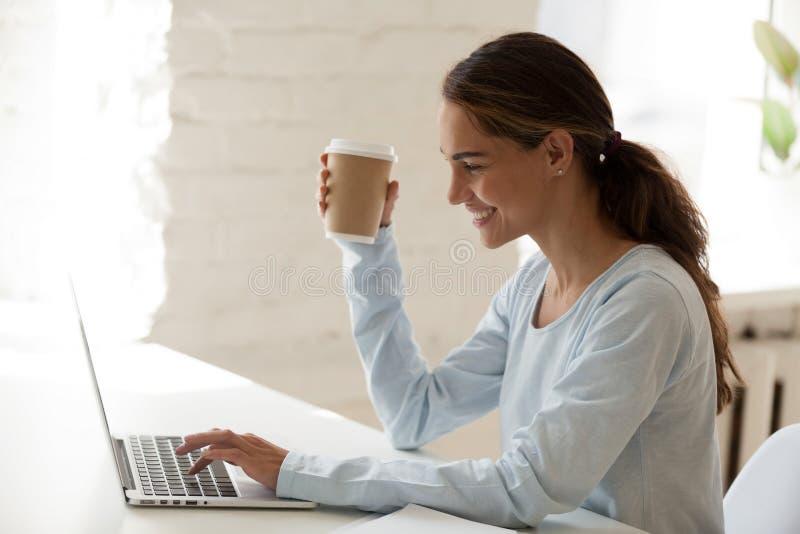 Mujer feliz sonriente que usa el ordenador portátil y bebiendo el café foto de archivo