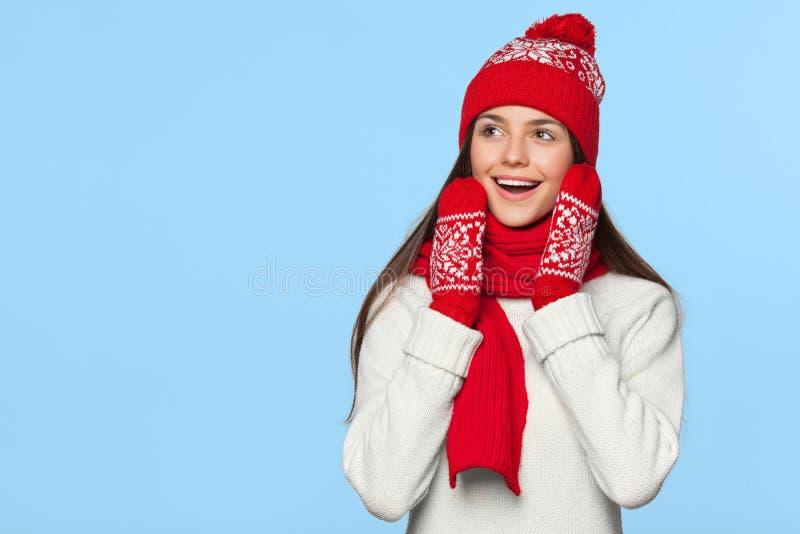 Mujer feliz sorprendida que mira de lado en el entusiasmo Muchacha de la Navidad que lleva el sombrero hecho punto y la bufanda c imagen de archivo