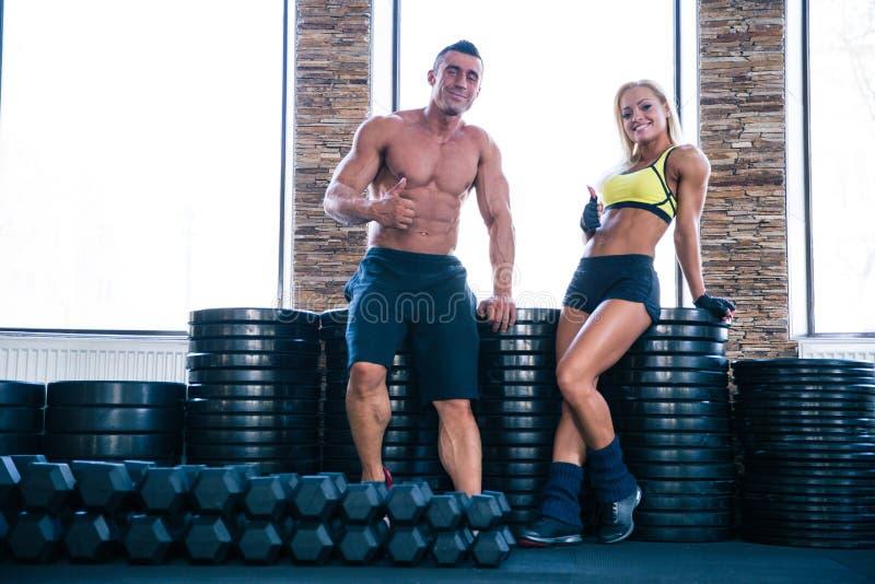 Mujer feliz y hombre del ajuste que muestran el pulgar para arriba en gimnasio foto de archivo