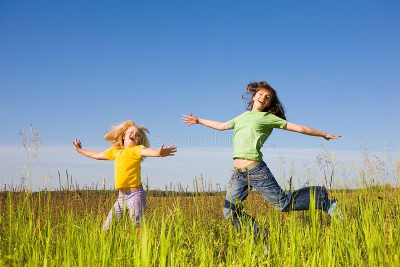 Mujer feliz y muchacha que hacen ejercicios en campo imagenes de archivo
