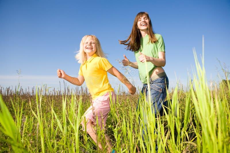 Mujer feliz y muchacha que hacen ejercicios en campo fotografía de archivo libre de regalías
