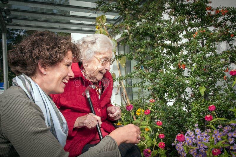 Mujer feliz y nieta mayores que se divierten en el jardín fotos de archivo