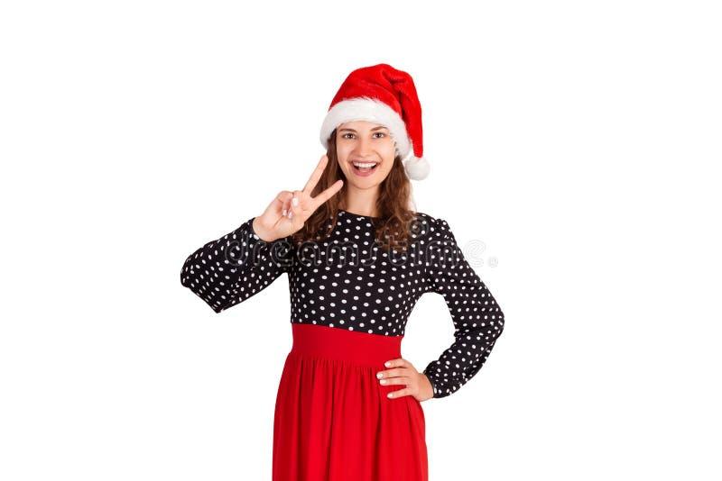Mujer feliz y saliente confiada en el vestido, mostrando la victoria o el gesto de la paz y guiñando con sonrisa amplia en la cám fotos de archivo
