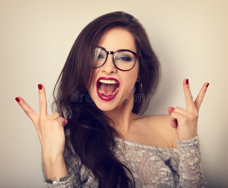 Mujer femenina feliz joven en vidrios con la demostración amplia abierta de la boca imagenes de archivo
