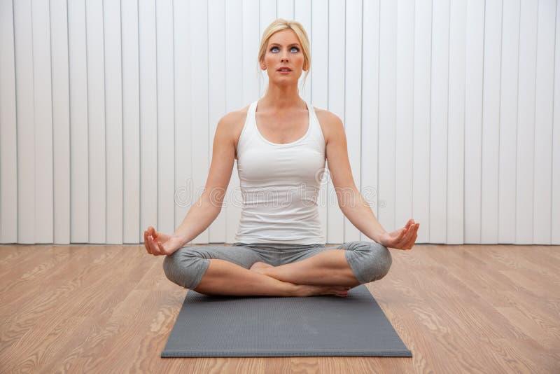 Mujer femenina joven que practica la posición asentada de la yoga imagen de archivo
