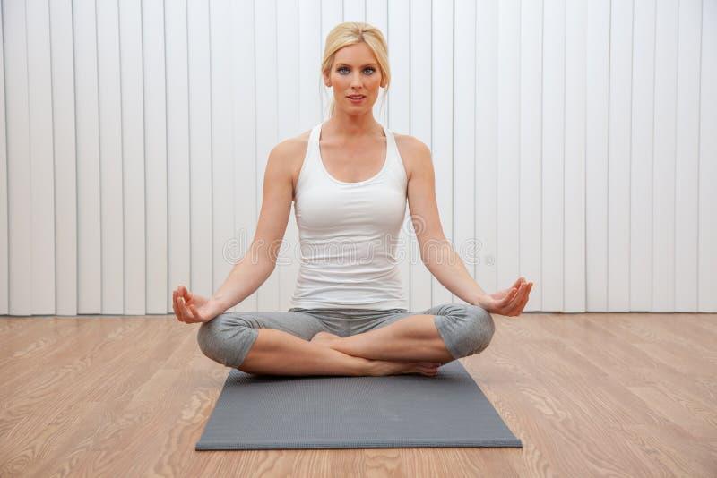 Mujer femenina joven que practica la posición asentada de la yoga foto de archivo libre de regalías