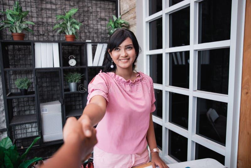 Mujer femenina joven que sacude la mano en su oficina imagen de archivo