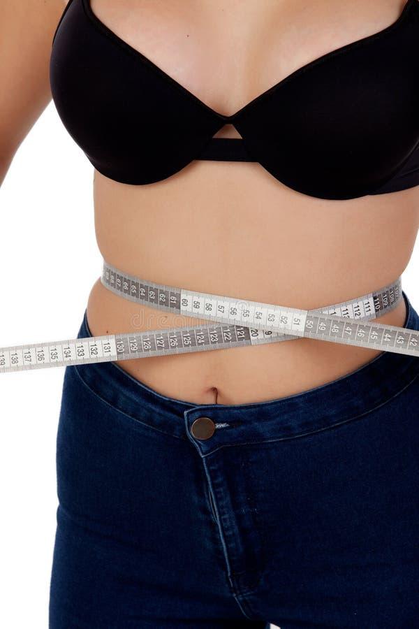 Mujer fina con el sujetador negro que mide su cintura foto de archivo