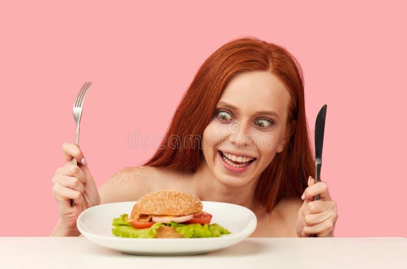 Mujer flaca pelirroja con los ojos codiciosos que son hamburguesa preparada foto de archivo libre de regalías