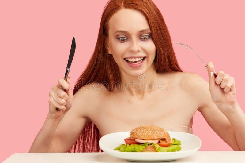 Mujer flaca pelirroja con los ojos codiciosos que son hamburguesa preparada fotos de archivo libres de regalías
