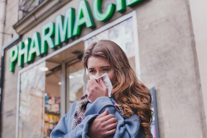 Mujer fría enferma al lado de una farmacia, concepto de la gripe foto de archivo