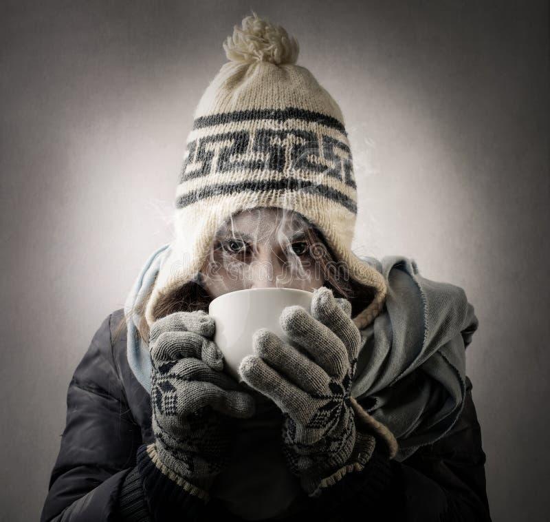 Mujer fría que bebe un café imagen de archivo