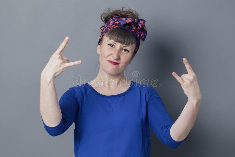 Mujer fresca 30s que hace el gesto de mano del heavy por satisfacción intrépida imagen de archivo libre de regalías