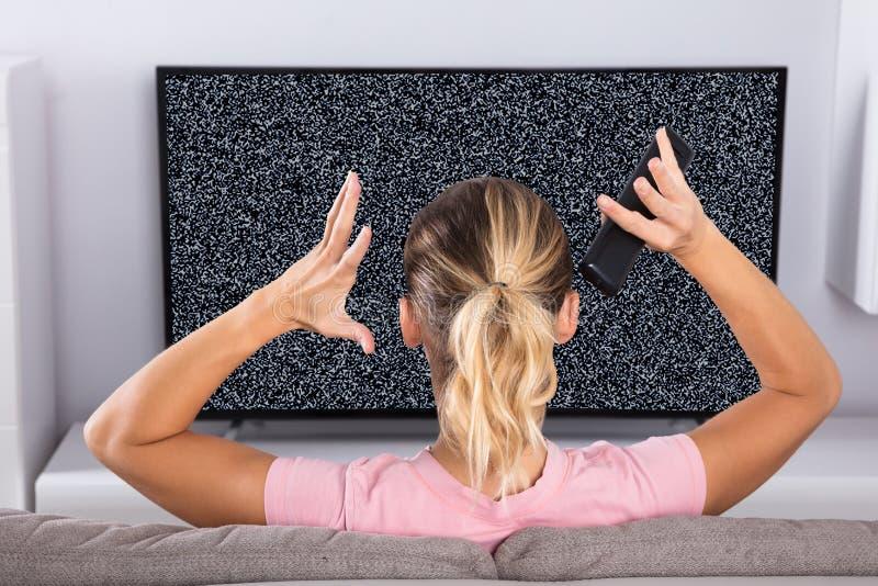 Mujer frustrada con una interferencia de la pantalla de la TV fotos de archivo libres de regalías