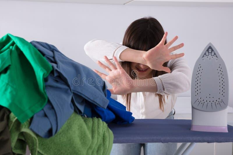 Mujer frustrada en Front Of Ironing Board imágenes de archivo libres de regalías