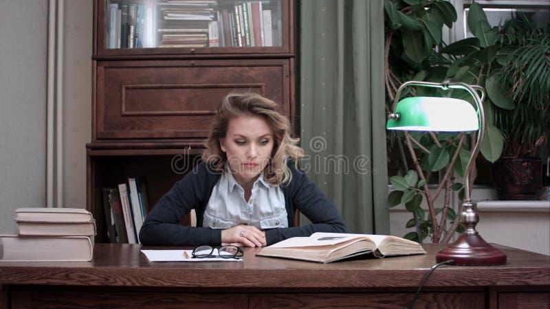 Mujer frustrada que mira impacientemente los papeles y los libros en su escritorio que se cierra de golpe los puños en la tabla fotografía de archivo