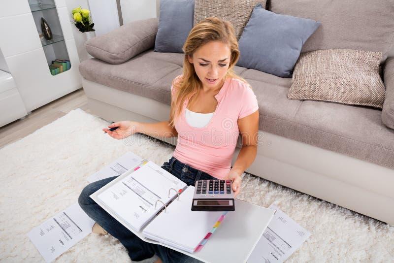 Mujer frustrada que mira la calculadora imágenes de archivo libres de regalías