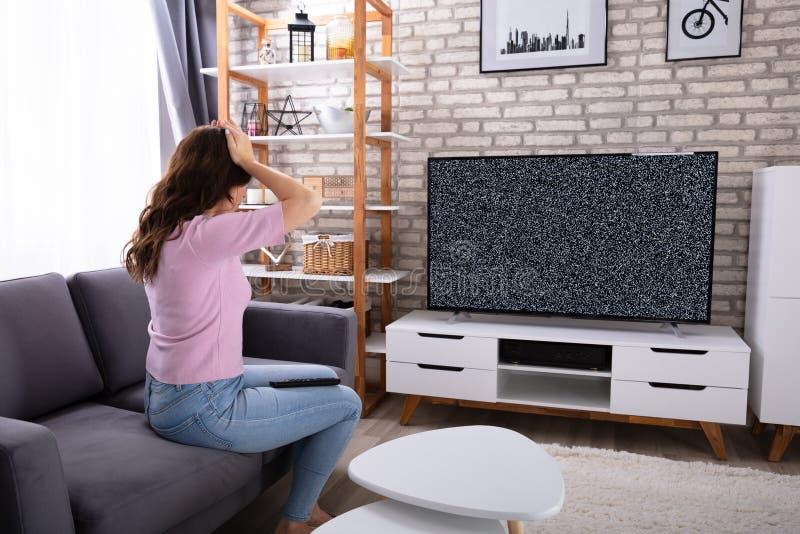 Mujer frustrada que mira la televisi?n sin se?al imágenes de archivo libres de regalías