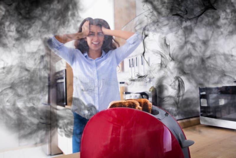 Mujer frustrada que mira la tostada quemada que sale de la tostadora imágenes de archivo libres de regalías